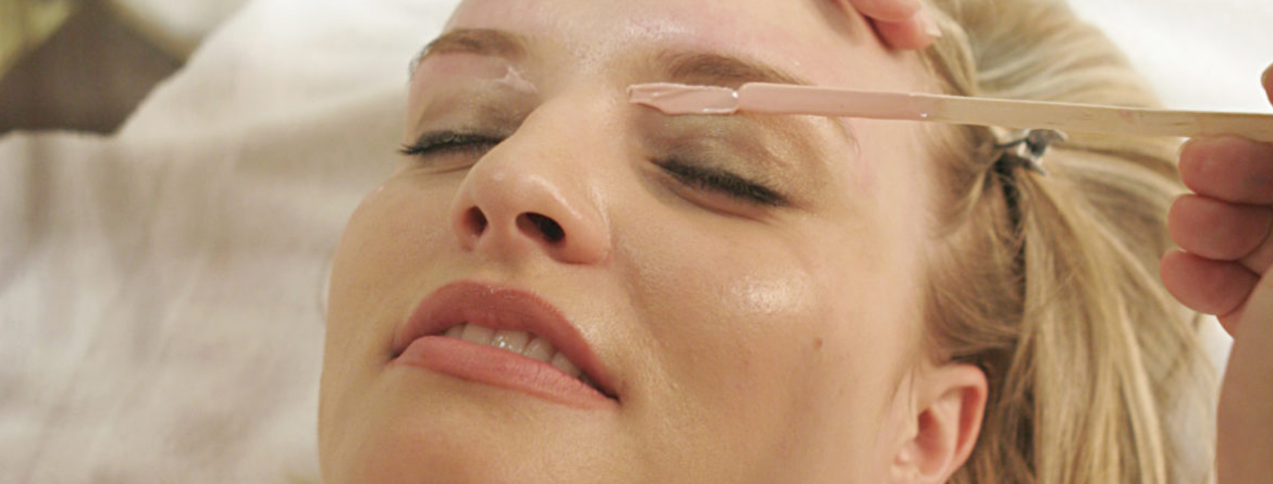 woman getting wax applied under eyebrow