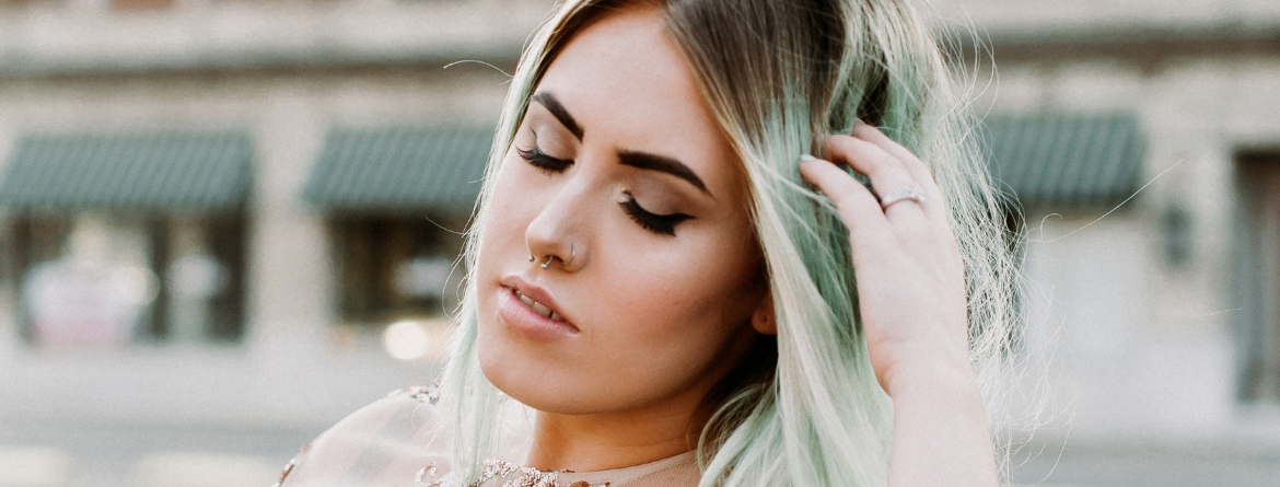 pretty woman with mint colored hair closing eyes to show off her eye makeup and long lashes