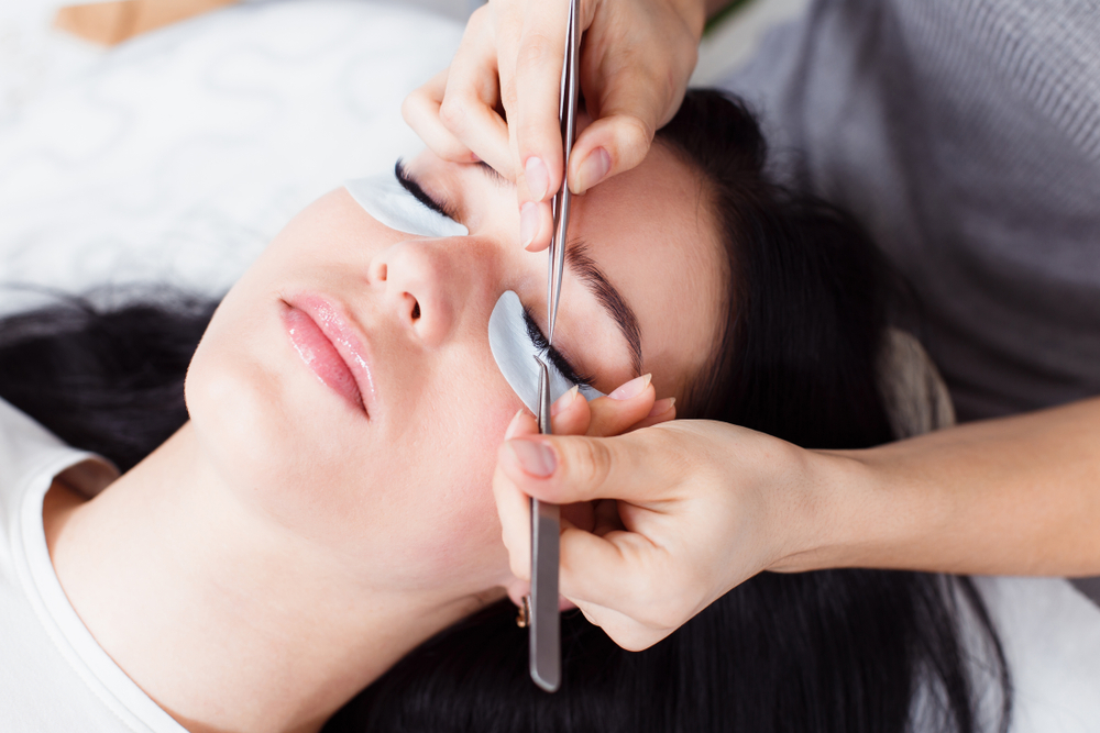 woman getting eyelash extensions at the salon