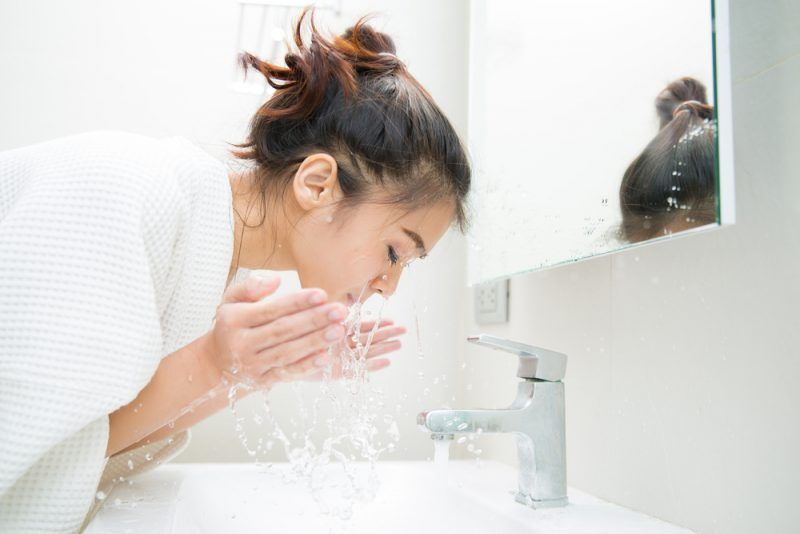 woman washing her face in the sink