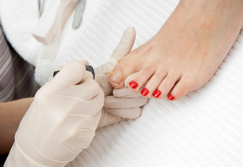 Woman getting her toenails painted red.