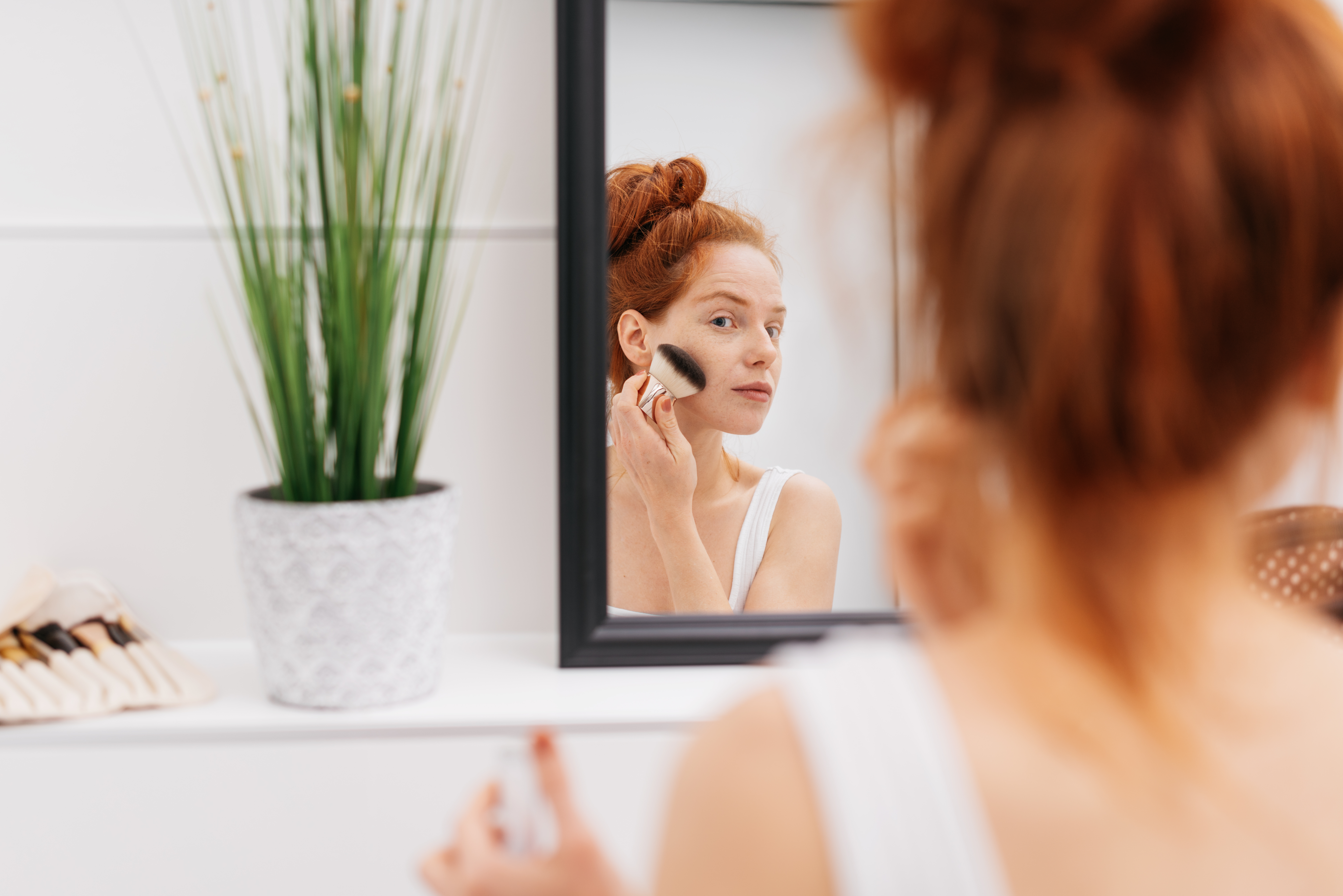 Woman applying makeup in the mirror