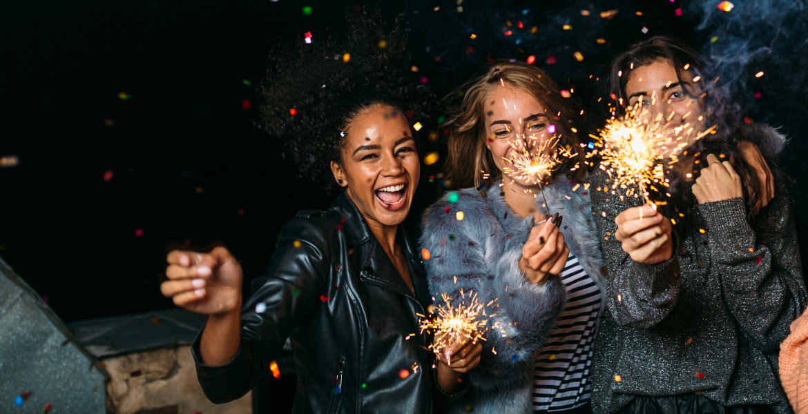 three girls smiling with sparklers and confetti