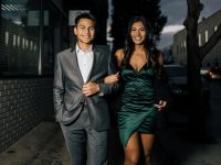 girl in a formal green dress walking arm in arm with a boy in a suit