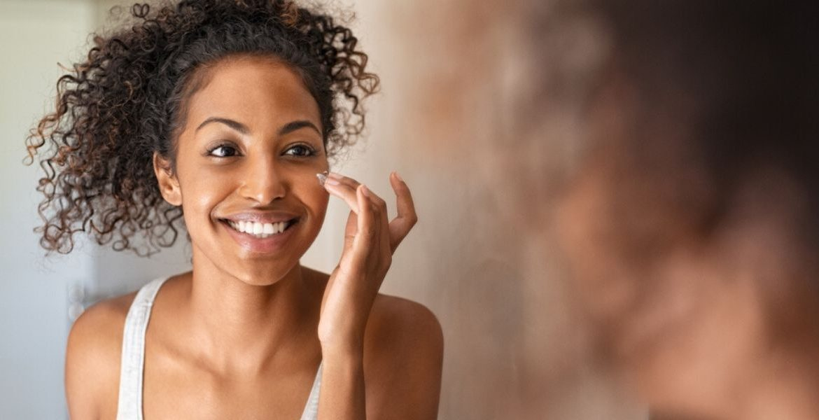 Woman smiling at herself in a mirror putting on product