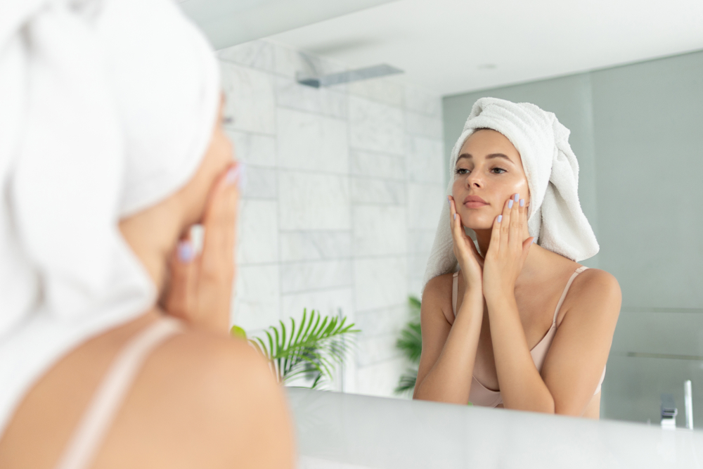woman looking at herself in the mirror and washing her face.