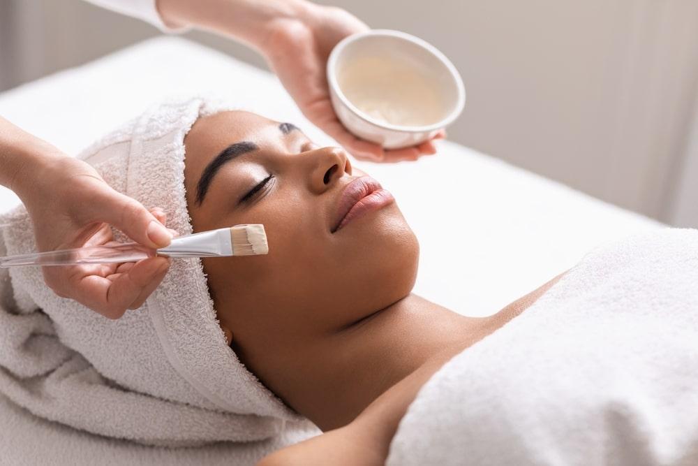 Woman having a facial applied.