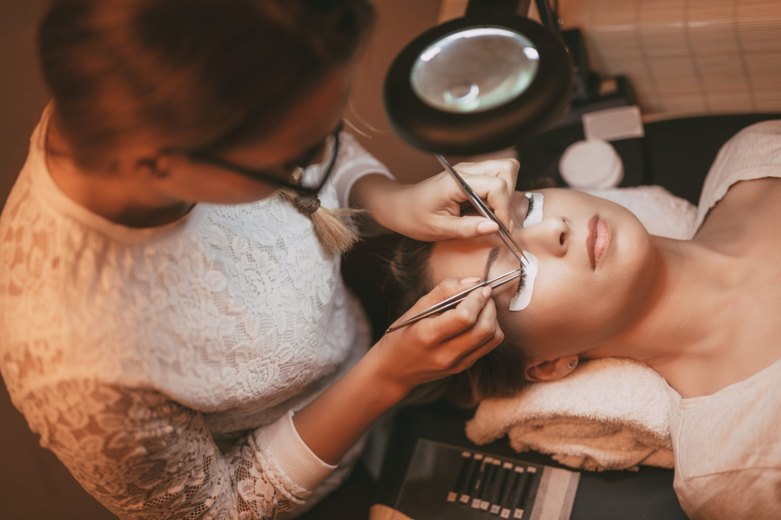 Beautician applying extended eyelashes to model at the beauty salon.