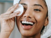 woman smiling and wiping off her makeup with a cotton pad